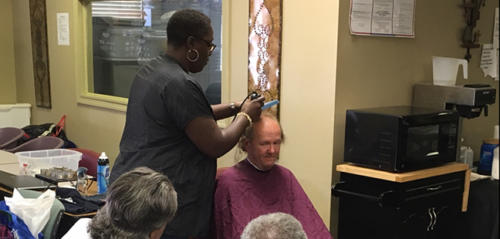 Guest in our Day Center Receiving Free Haircuts from a Volunteer